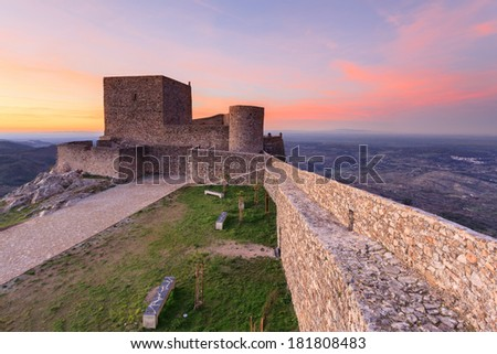 Medieval castle overlooking the Alentejo plains at sunset.