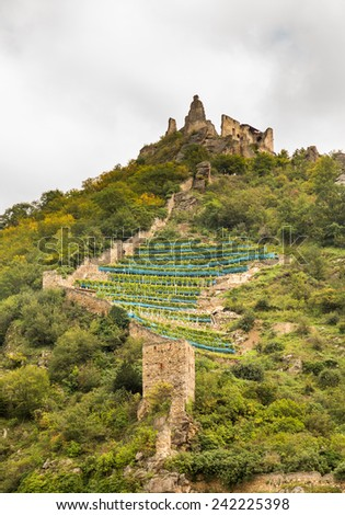 Medieval castle ruins on hillside above town by River Danube in Durnstein, Austria - stock photo