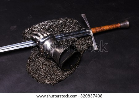 Medieval chain mail, iron gauntlet and a bastard sword still life on a dark background - stock photo