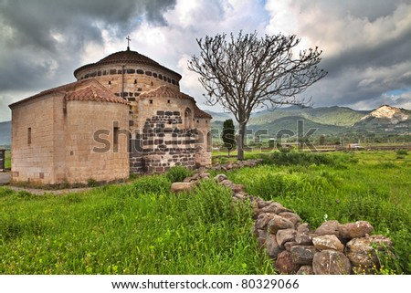 Medieval church Santa Sabina in Sardegna Italy with dark clouds historical building sardinia Italy travel and tourism history - stock photo