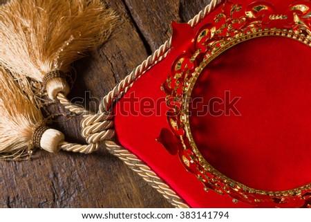 Medieval golden king's crown on red velvet pillow - stock photo