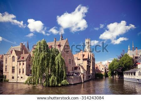 medieval houses, Rozenhoedkaai in Brugge, Dijver river canal and Belfort (Belfry) tower, West Flanders. Instagram style filtred image - stock photo