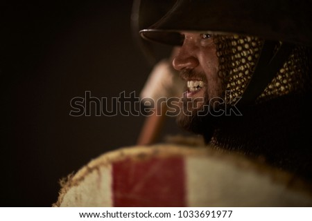 Medieval infantry man charging for attack. Historical re-enactment scene with authentic clothing and props