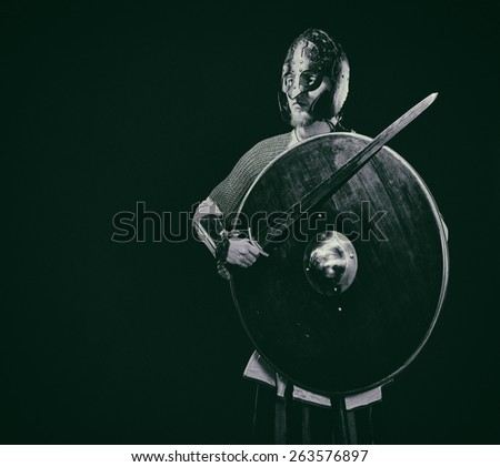 Medieval knight armor with a sword, helmet and shield, black and white image