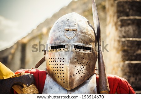 Medieval knight in helmet on ancient wall background - stock photo