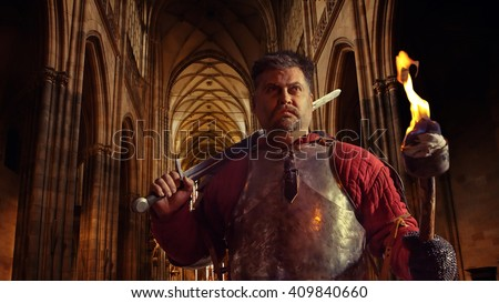 Medieval knight in the armor with the sword and flame on the ancient (more than 1000 years, no property release needed) St. Vitus Cathedral interior, Prague, Check Republic.