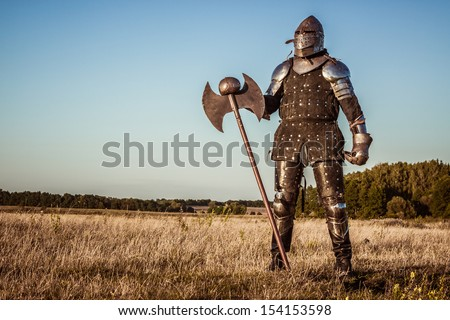 Medieval knight in the field with an axe - stock photo