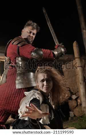 Medieval knight is going to make an execution of a witch. Witch house on the background. - stock photo