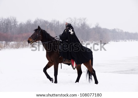 Medieval knight of St. John (Hospitallers) on a bay horse - stock photo