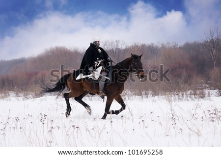 Medieval knight of St. John (Hospitallers) riding on a bay horse - stock photo