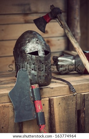 Medieval knight's helmet and various weapon, vertical shot - stock photo