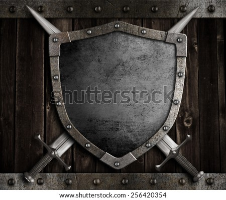 medieval knight shield and crossed swords on wooden gate - stock photo