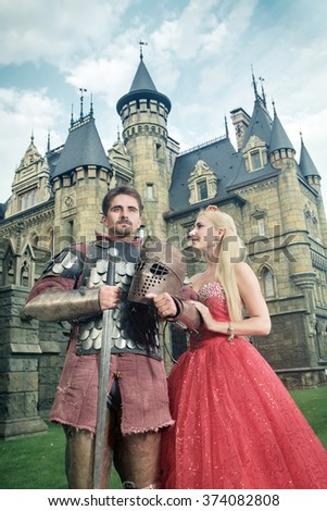 Medieval knight with his beloved lady. Ancient castle on the background.