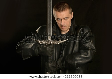 Medieval knight with sword on a dark background - stock photo
