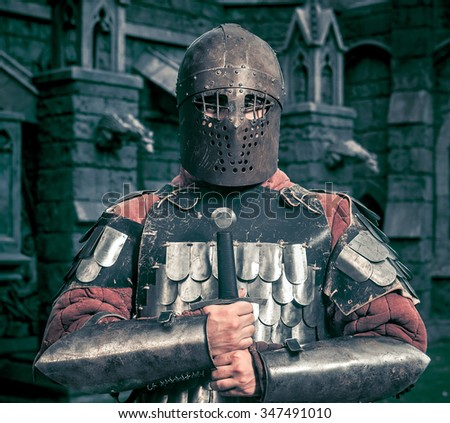 Medieval knight with the sword on the ancient castle background - stock photo