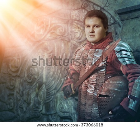 Medieval knight with the sword on the ancient castle background. Artistic toning. - stock photo