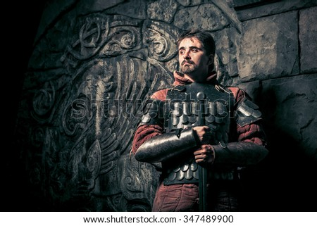 Medieval knight with the sword on the ancient castle background. Low contrast post processing. - stock photo