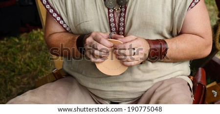 Medieval leatherworker makes leather mug for kitchen decoration - stock photo