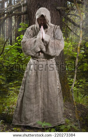 Medieval monk praying in the misty forest - stock photo