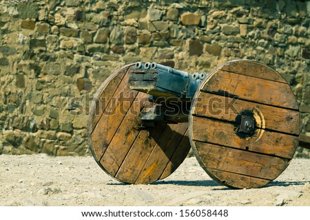 Medieval multi-barrelled cannon against stone wall of ancient Italian fortress  - stock photo