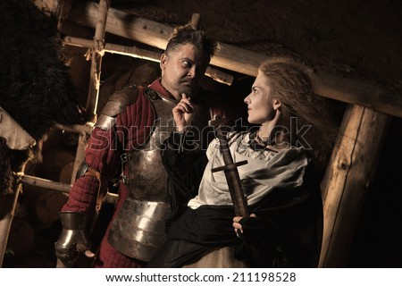 Medieval peasant woman is flirting with the knight. Wooden house on the background.