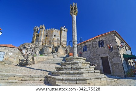 Medieval pillory used for attaching criminals to and administering punishments, with castle in the background. In Penedono, northern Portugal - stock photo