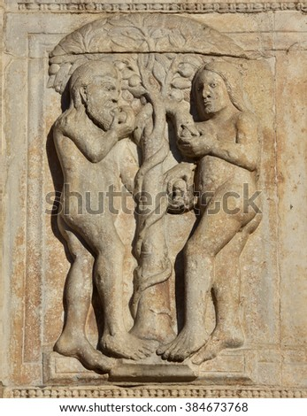 Medieval relief of Adam, Eve, the snake and the tree of knowledge from Basilica of San Zeno facade, in Verona (12th century) - stock photo