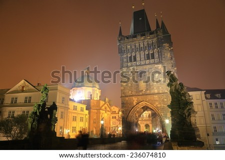 Medieval sculpture and tower on the Charles bridge illuminated by night, Prague, Czech Republic - stock photo