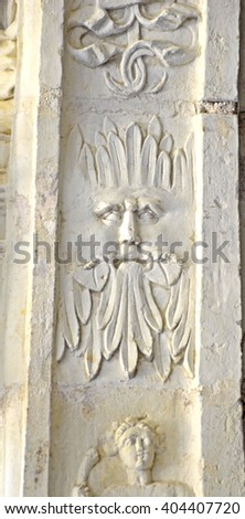 Medieval sculpture of a man's face mixed with leaves, known as a foliate head with pagan significance - stock photo
