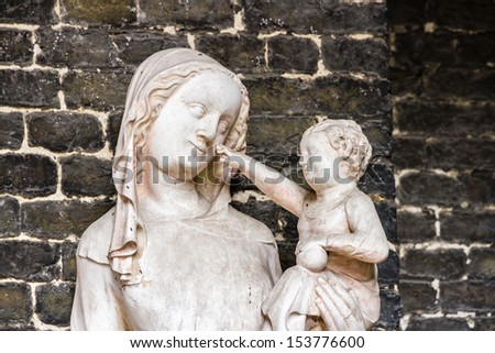 Medieval sculpture of the virgin Mary with the Christ Child on her arm who is pointing at her face. - stock photo