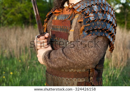 Medieval slav warrior man wearing in ancient armor with sword. Close up detail. - stock photo