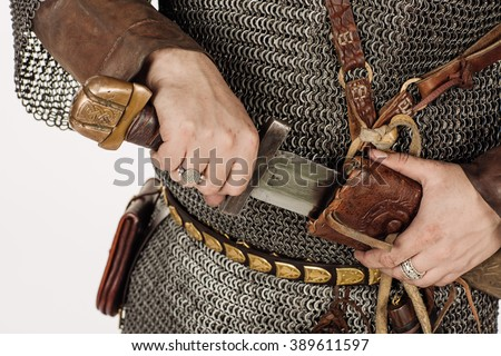 medieval slavic soldier standing and ready for a fight with sword, helmet, hauberks. image on white studio background. historical concept.