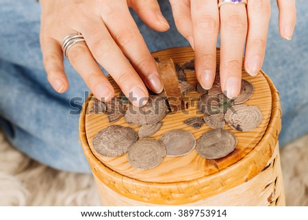 medieval slavic woman holding pile of old coins. image on white background. historical concept.