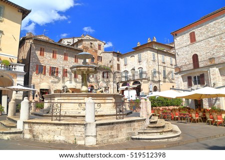 Medieval square with old water fountain and historical buildings, Assisi, Umbria, Italy