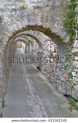 Medieval stone arches above long passage inside the town of Villefranche de Conflent in the Conflent region of Catalonia, Pyrenees-Orientales department, France - stock photo