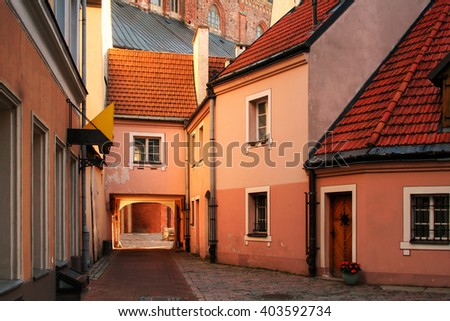 Medieval street in old Riga city. Riga is the capital and largest city of Latvia, a major commercial, cultural, historical and financial center of the Baltic region. - stock photo