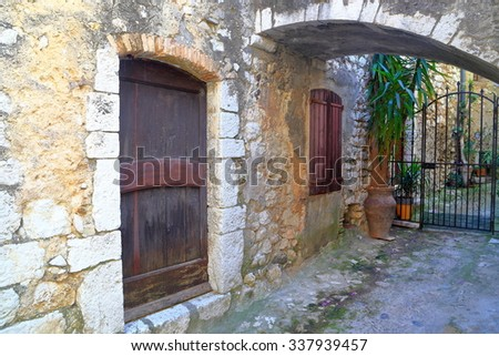 Medieval street with aged walls and door in the old town of Saint Paul De Vence, France