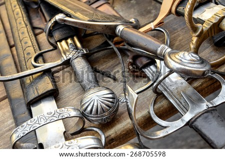 medieval swords on a wood table - stock photo