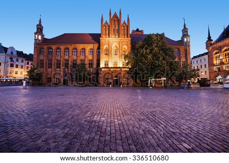 Medieval Town Hall and square in the Old Town of Torun, Poland, city landmark at dusk.