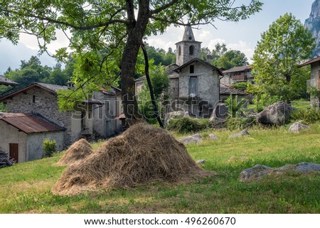 Medieval Village with Haystack: A haystack in front of buildings of an old village