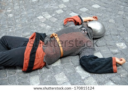 medieval warrior lying dead on the ground - stock photo