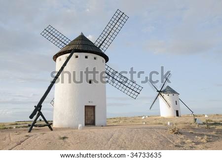 "Medieval windmills on a hill overlooking the town of Campo de Criptana, Castilla la Mancha, Spain. They appear in the famous novel ""Don Quixote de la Mancha"", wrote by Miguel de Cervantes - stock photo"