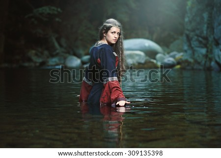 Medieval woman in the middle of a dark stream. Fantasy and fairy