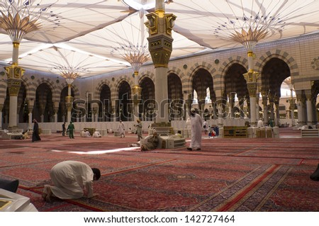 MEDINA-FEB 17:Muslims read Quran and pray inside of Masjid Nabawi Feb 17, 2012 in Medina, Saudi Arabia. Nabawi Mosque is the second holiest mosque in Islam and here is Prophet Muhammad is laid to rest - stock photo