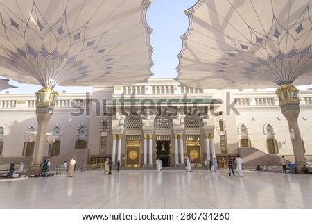 MEDINA - MARCH 06 : Pilgrims walk underneath giant umbrellas at Nabawi Mosque compound on March 06, 2015 in Medina, Kingdom of Saudi Arabia. Nabawi mosque is the second holiest mosque in Islam.  - stock photo