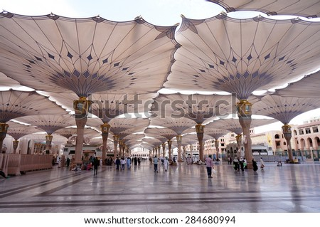 MEDINA, SAUDI ARABIA-CIRCA MAY 2015: Pilgrims walk underneath giant canopies in Nabawi Mosque on MAY, 2015 in Medina, Saudi Arabia .The Nabawi mosque is the second holiest mosque in Islam. - stock photo