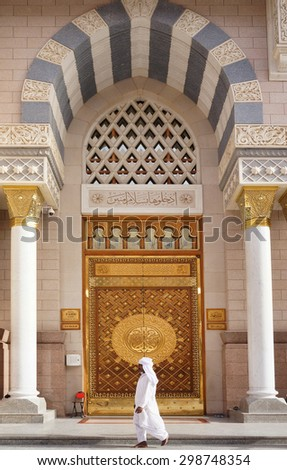 MEDINA,SAUDI ARABIA -CIRCA MAY 2015 : unidentified man walking in front of the King Fahd Door of Masjid Nabawi on May, 2015 in Medina, Saudi Arabia. Nabawi Mosque is the second holiest mosque in Islam - stock photo