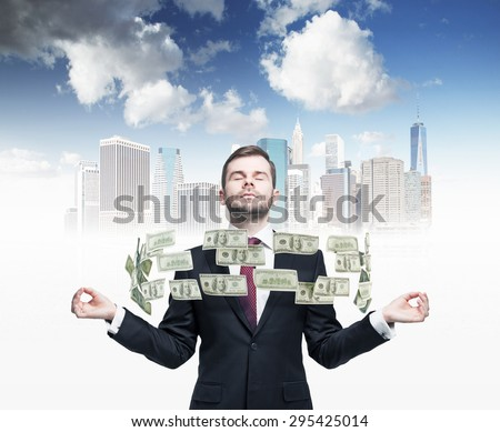 Meditating businessman and flying dollar notes between his hands. A sketch of New York city on the background.