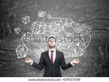 Meditating businessman standing against chalkboard with connected dice sketch. Game and probability theory - stock photo