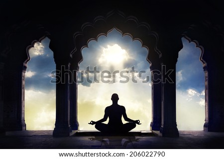Meditating in old temple with decorative arches at dramatic sunset sky with light hole in the clouds - stock photo